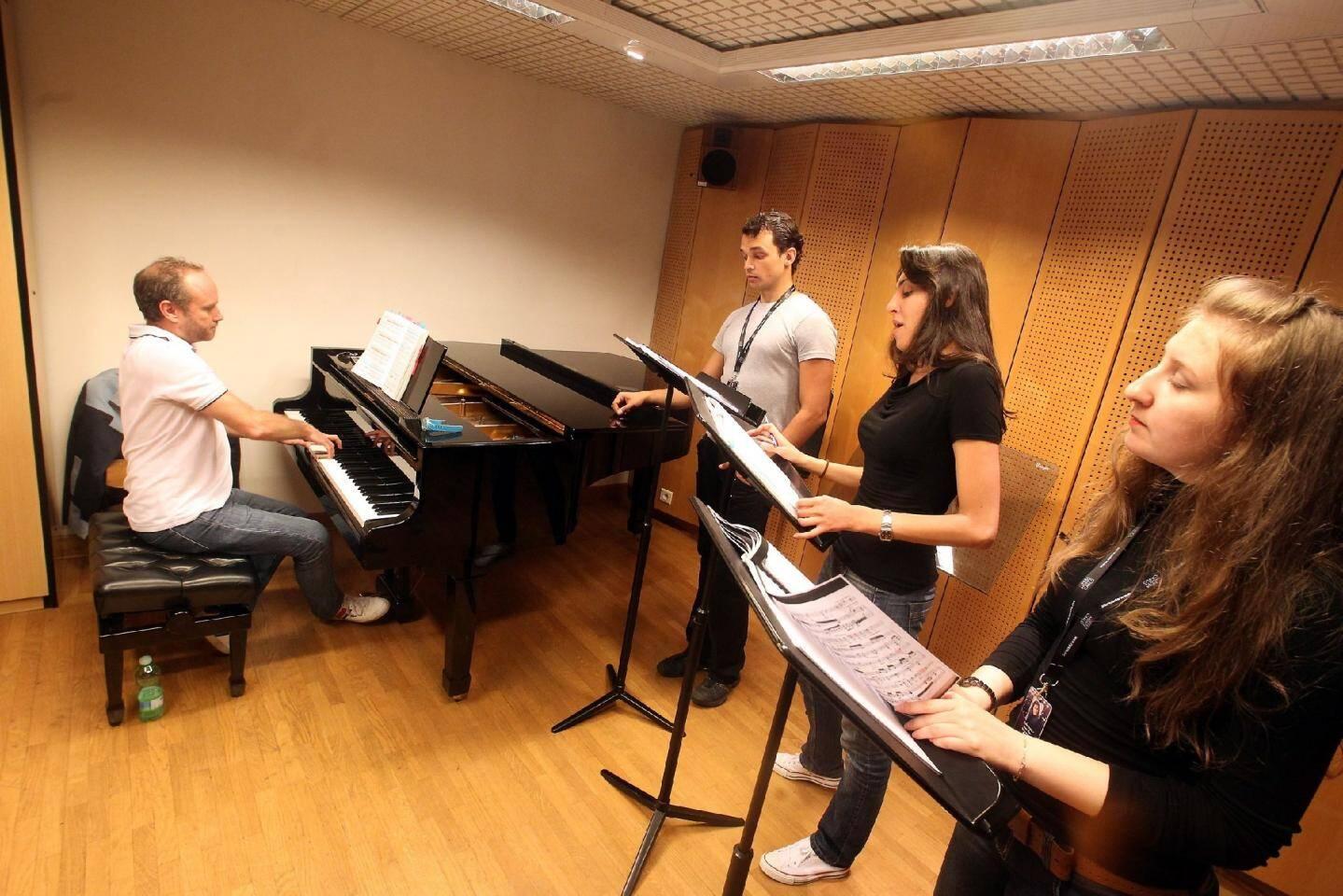 Autour du piano d'Antoine Palloc, instant de répétitions pour le baryton Ilia Lapitch, accompagnée par Karina Demourova et Diana Aïssina sur une partition de Massenet. Dans une autre salle Anastacia Medvedeva, suit une partition, elle en italien.