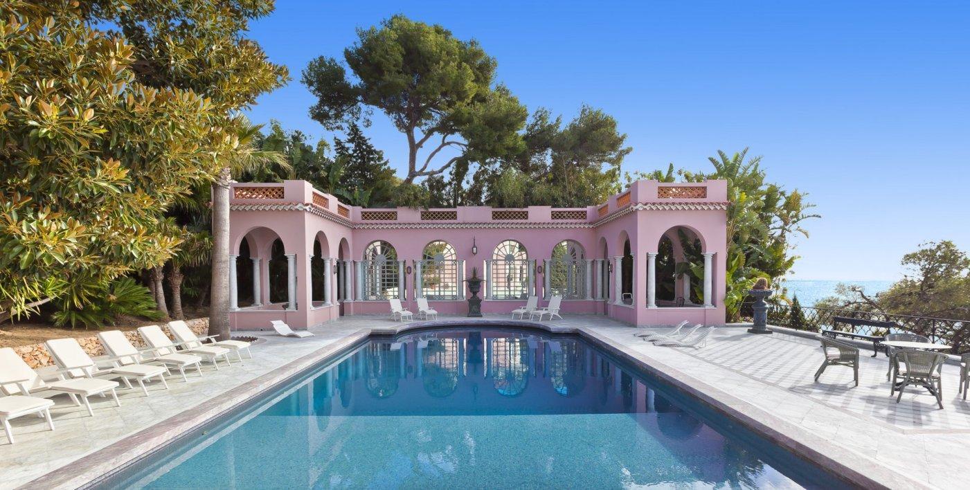 La piscine de près de 20 mètres de long est entourée d'arbres luxuriants à quelques mètres de la mer.