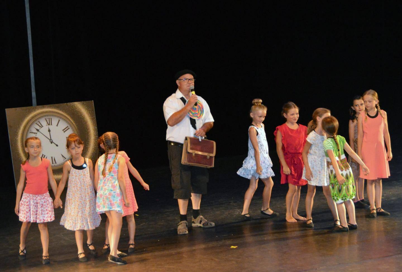 Enfants et adultes ensemble sur la scène dans un partenariat réussi.
