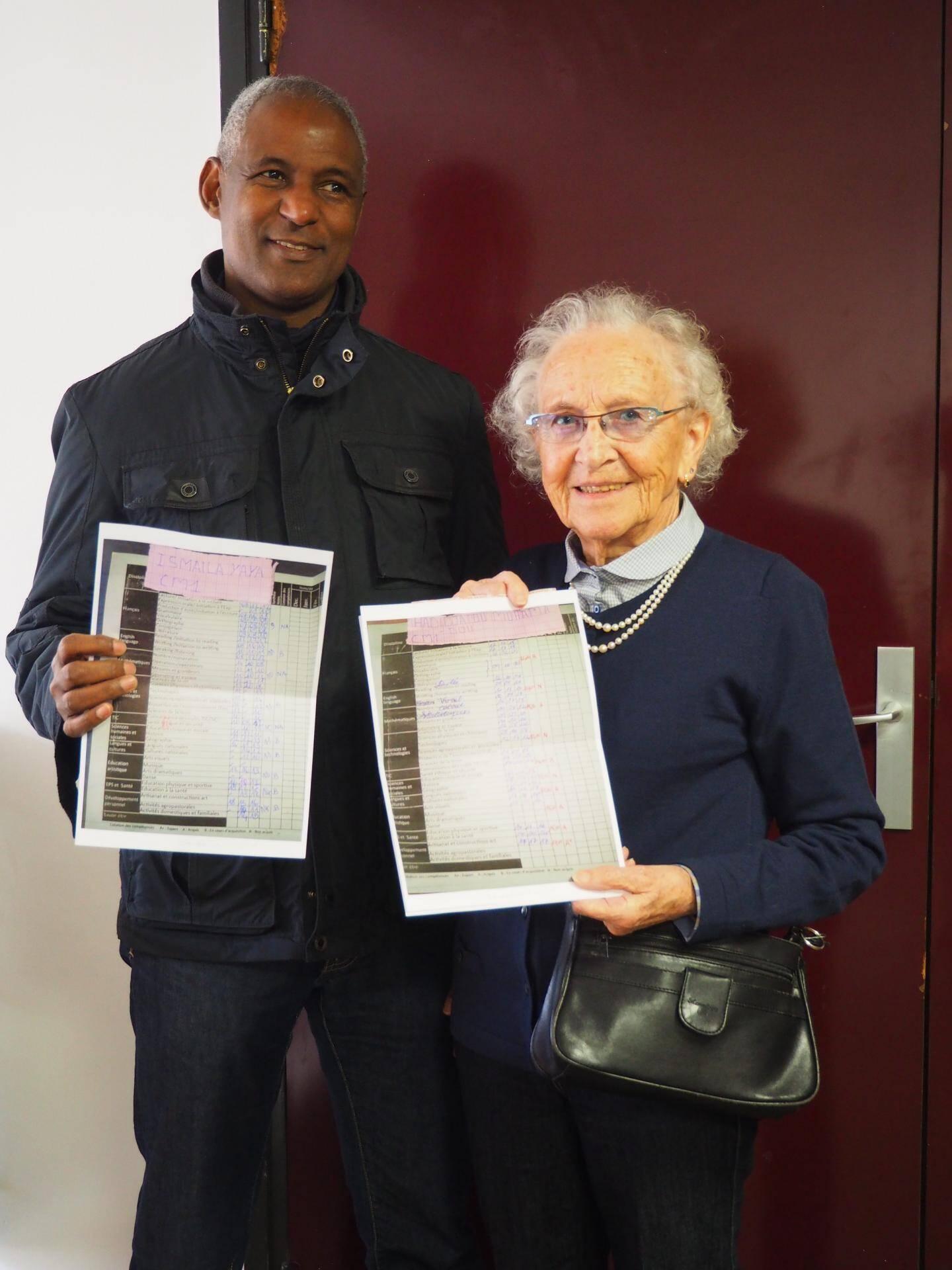 Jackie est très fière de montrer au président les bulletins fraîchement reçus de Hadidjatou et Ismaïla, deux enfants en CM1 qu'elle parraine.