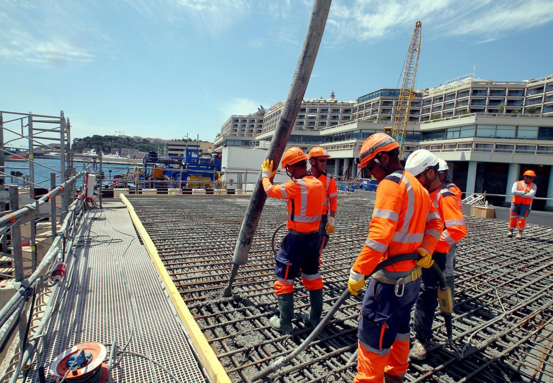 Des ouvriers coulent une dalle de béton sur l'un des caissons de l'extension en mer. C'est le démarrage des travaux de génie civil, destinés à couvrir ces parpaings géants de 10 000 tonnes.