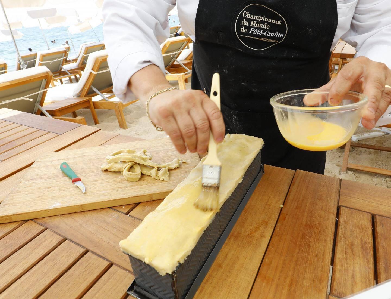 Avant de cuire son pâté-croûte, Daniel Gobet badigeonne la pâte d'un mélange de jaune d'œuf et de sirop.