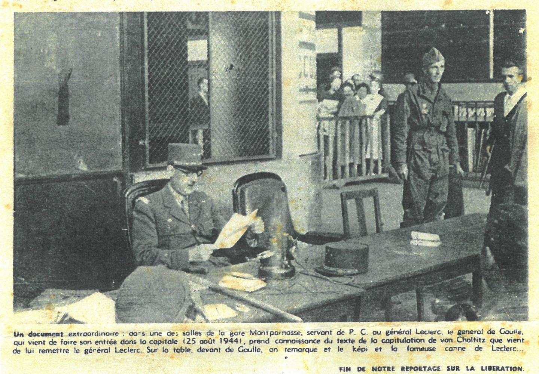 Émile Vacek (à droite chemise blanche, arme sous le bras), regarde le Général de Gaulle qui consulte l'acte de reddition de l'armée allemande à Paris.