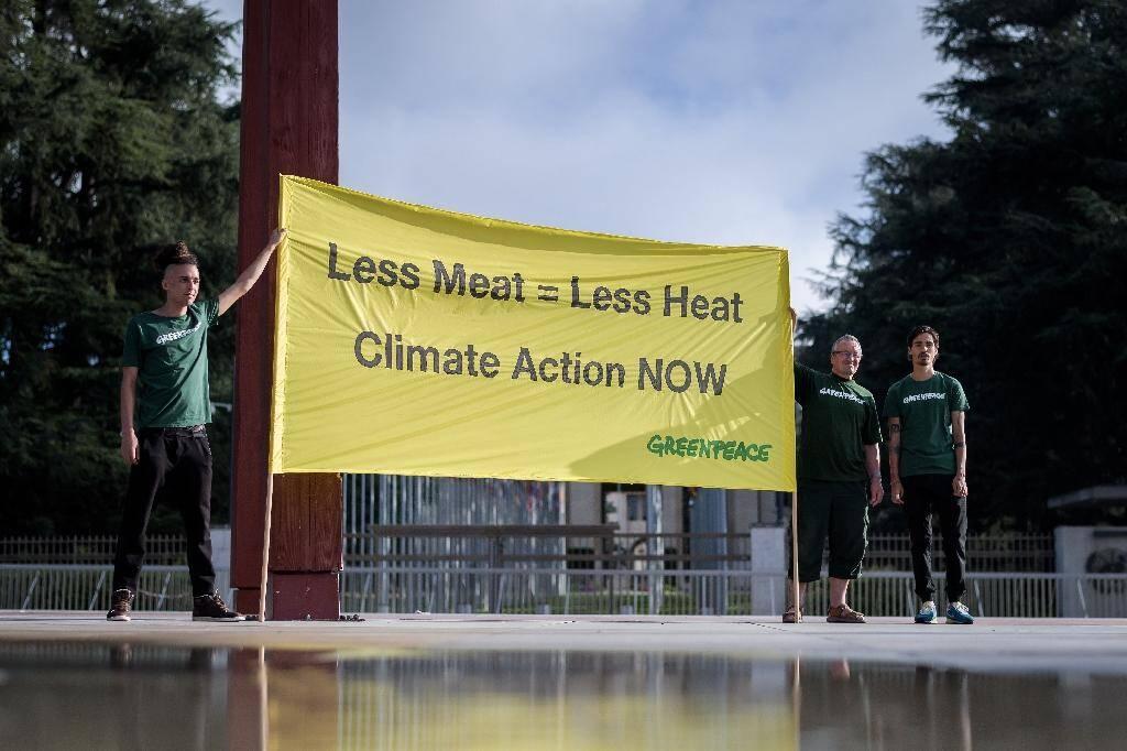"""""""Moins de viande = moins de chaleur, Action pour le climat maintenant"""" sur une banderole brandie par des militants de Greenpeace, le 8 août 2019 à Genève, avant la publication du rapport du Giec sur le climat et les terres"""