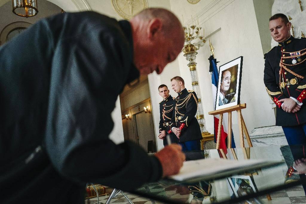 Un homme signe un registre de condoléances pour le président Jacques Chirac au Palais de l'Elysée, le 28 septembre 2019.