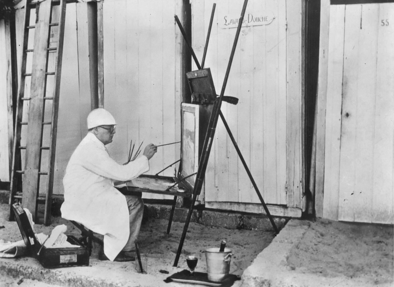 Winston Churchill à l'œuvre face à son chevalet devant les cabines de bains de la Garoupe en septembre 1935 avec tout son matériel de peintre dans sa valise sans oublier le seau à champagne dont il était amateur.