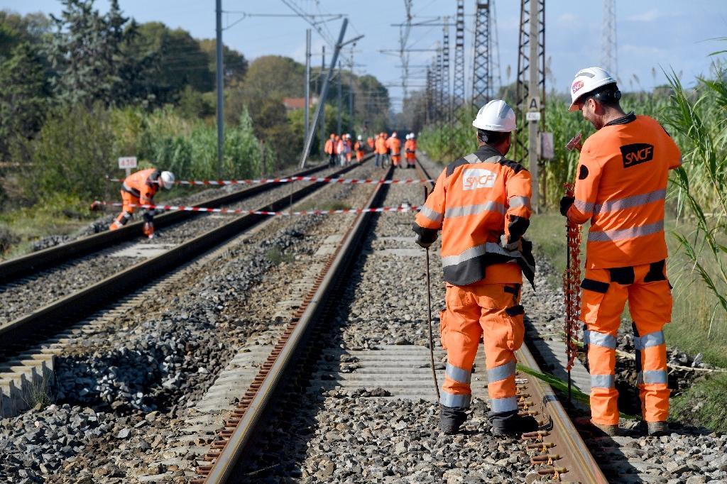 Des salariés de la SNCF inspectent les rails après de violents orages à Villeneuve-les-Beziers, dans le sud de la France, le 24 octobre 2019