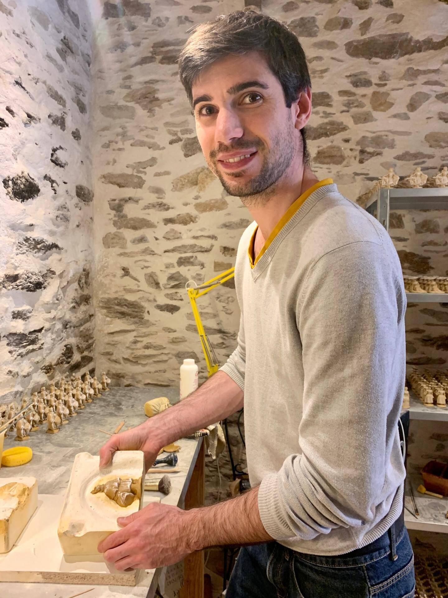 Une fois l'argile compactée et moulée, Maxime Codou s'apprête à sortir sa dernière pièce.