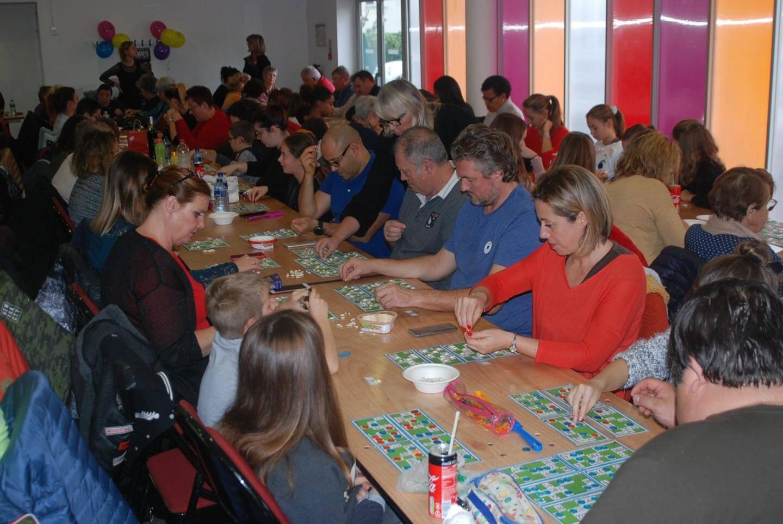 Concentrés, têtes baissées sur les cartons de jeu, les joueurs sont concentrés à l'énumération des numéros.