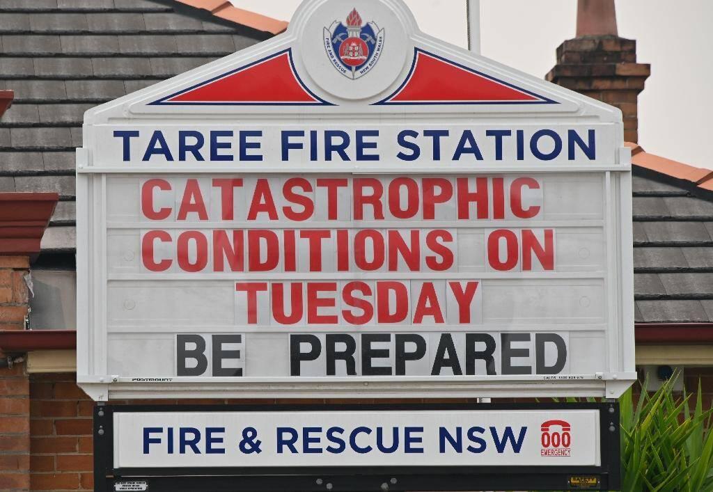 """""""Conditions catastrophiques mardi, préparez-vous"""", lit-on sur la caserne de pompiers de Taree Des carcasses calcinées de véhicules après des incendies de brousse à Old Bar à 350 kms au nord de Sydney le 11 novembre 2019"""