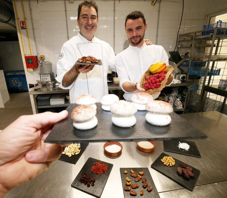 Patrick Pomares et Maxime Marecaux pris dans la farandole d'ingrédients - dont les champignons meringués à base de jus de pois chiches - qui vont constituer la bûche.