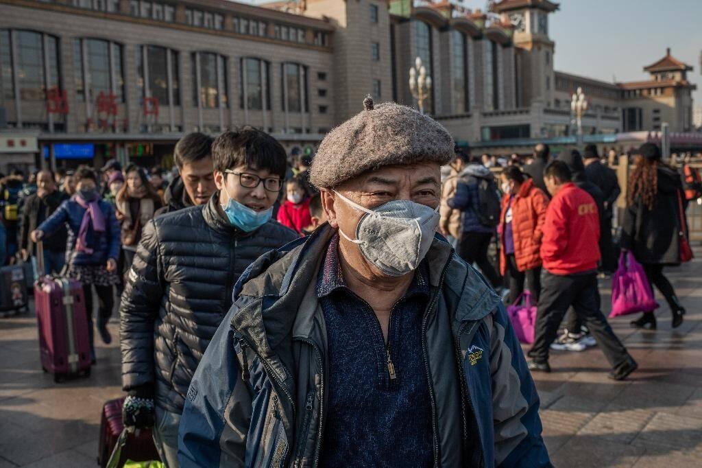 Des Chinois, un masque de protection sur le visage, arrivent à la gare de Pékin pour prendre un train et rendre visite à leurs familles à l'occasion des congés du Nouvel An, le 21 janvier 2020 en Chine