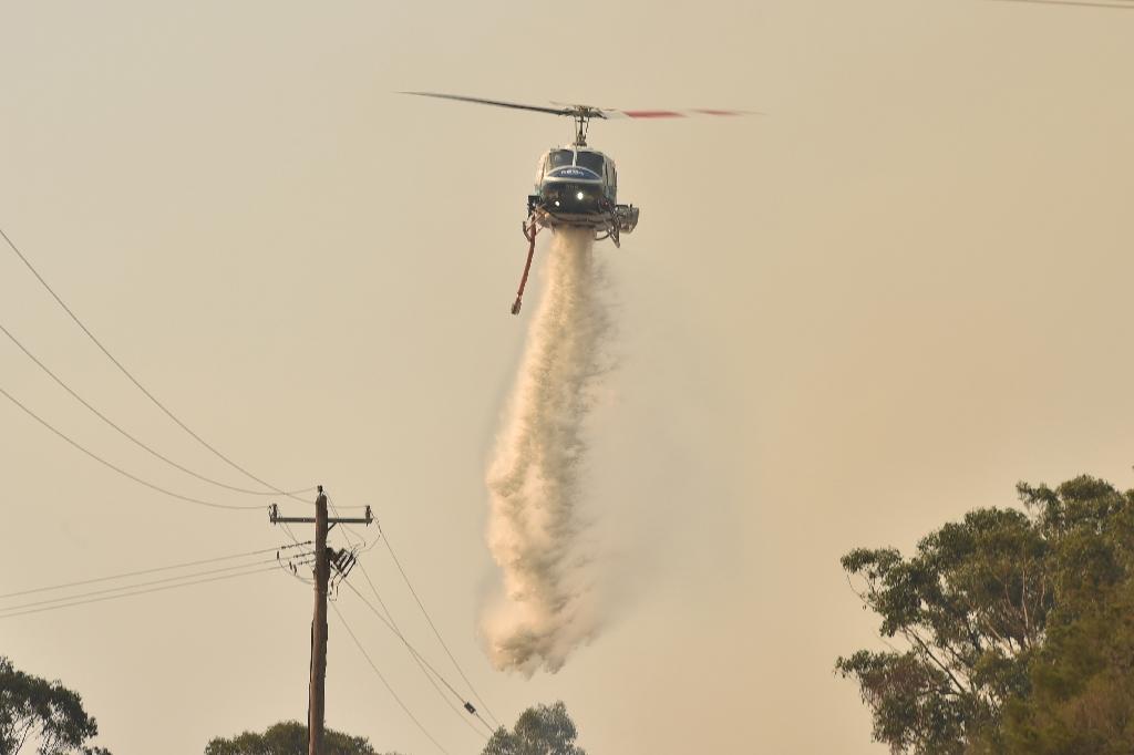 Un hélicoptère deverse de l'eau pour combattre les feux de forêts en Nouvelle-Galles du sud dans la baie de Batemans, le 4 janvier 2020
