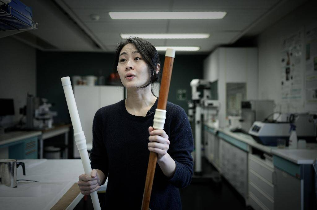 Mina Jang, chercheuse en musique baroqueet flûtiste professionnelle, tient un clone en 3D (g) d'une flûte traversière originale (d), le 17 janvier 2020 au laboratoire du musée de la musique de la Philharmonie de Paris
