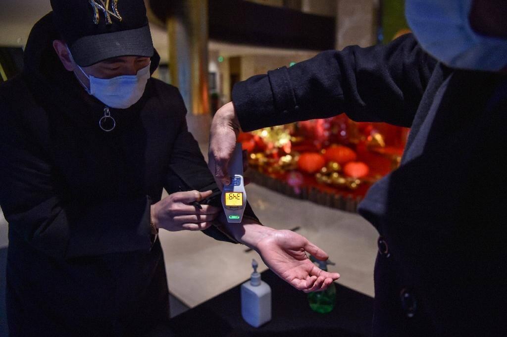 L'employé d'un hôtel de Wuhan contrôle la température d'un nouvel arrivant, le 24 janvier 2020