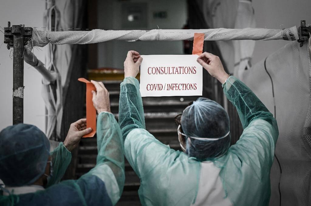 Des personnels soignants scotchent une affiche devant l'entrée d'un centre de test pour le Covid-19, le 27 mars 2020 à Paris