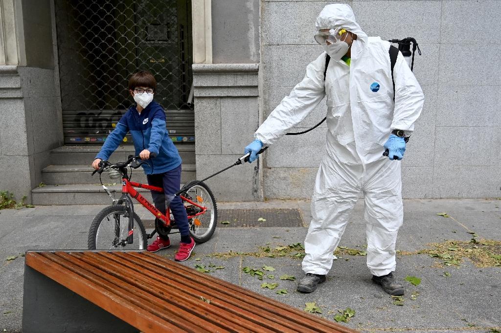 Un enfant et un employé chargé de la désinfection des rues à Madrid le 28 avril 2020