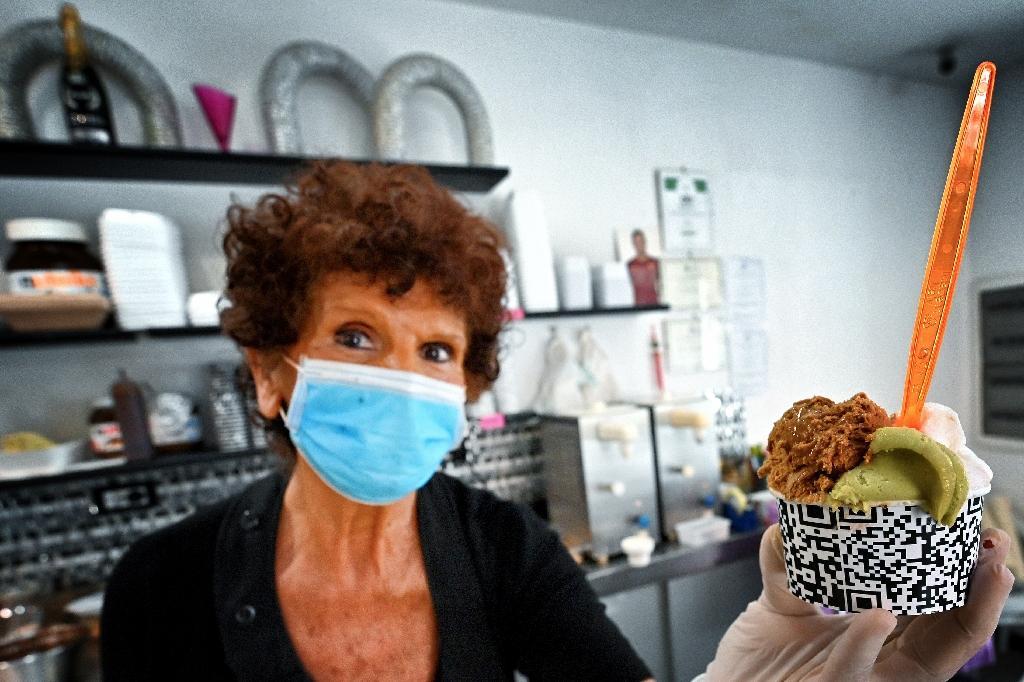 Maddalena sert une glace à un client chez Brivido dans le quartier de Testaccio à Rome alors que le pays a assoupli son confinement contre le coronavirus, le 26 mai 2020