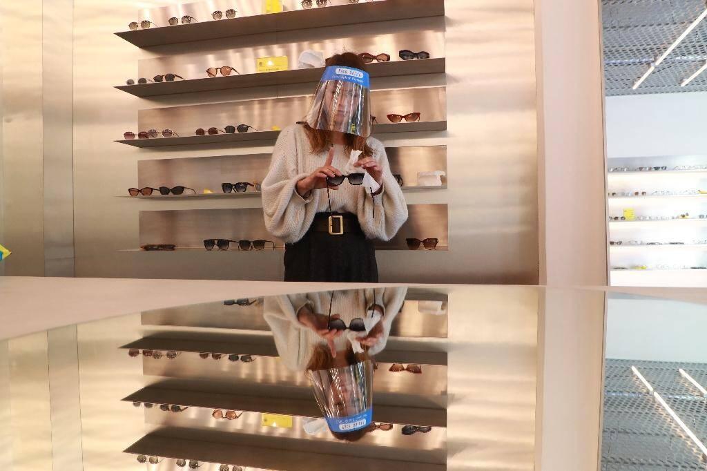 L'employée d'un magasin d'optique porte un masque avant l'ouverture, à Paris le 12 mai 2020