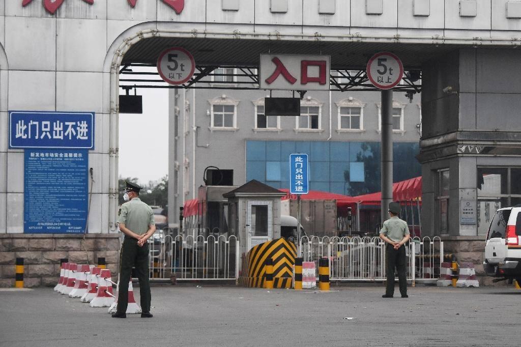 Des policiers chinois devant l'entrée du marché Xinfadi fermé, le 13 juin 2020 à Pékin, après l'apparition d'un nouveau foyer de coronavirus
