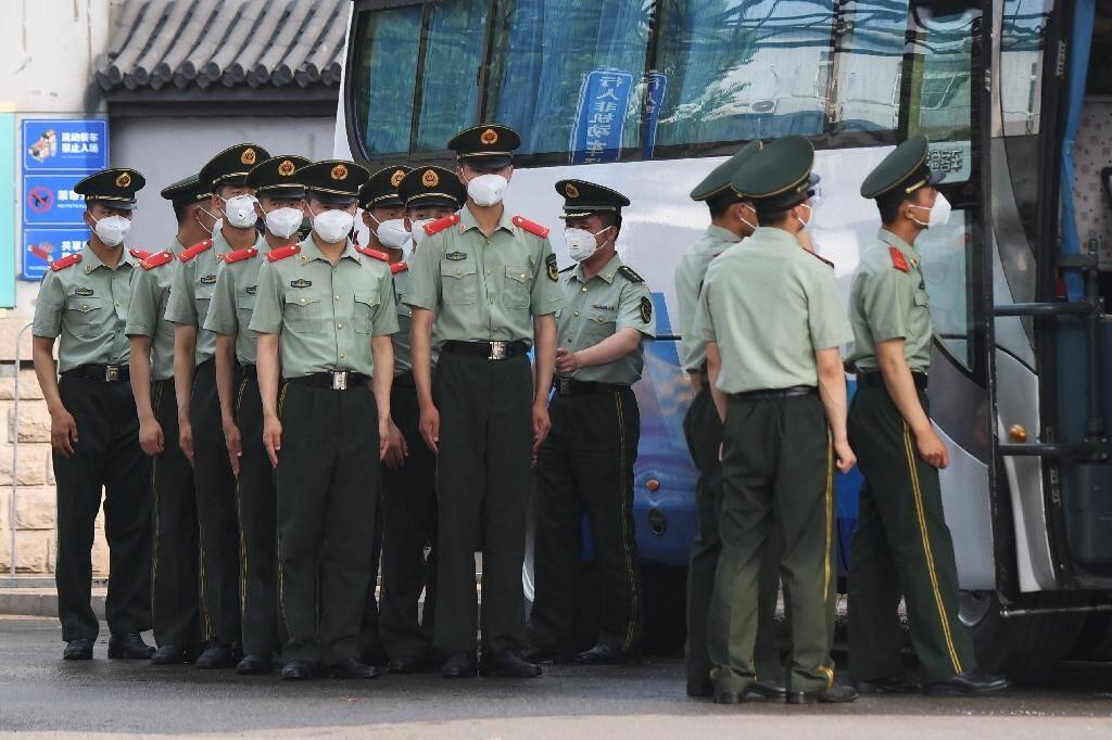 Des policiers chinois se préparent le 13 juin 2020 à garder les abords du marché Xinfadi à Pékin, fermé après la découverte de cas de coronavirus