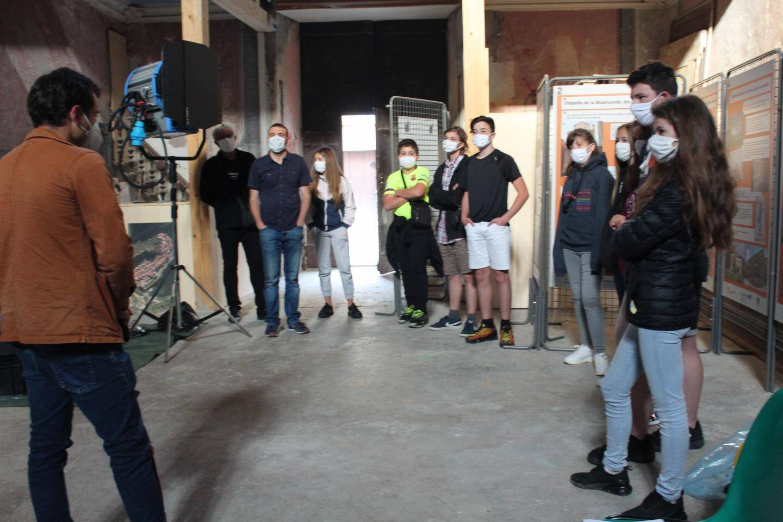Un membre de l'équipe du film explique le tournage aux collégiens.