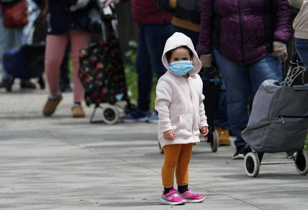 Des New-Yorkais font la queue pour de la nourriture gratuite à New York, durement éprouvée par la pandémie, le 18 mai 2020