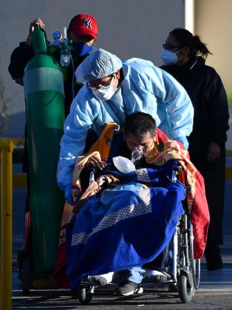 Une infirmière aide un patient infecté par le Covid-19 devant l'hôpital régional Honorio Delgado Hospital, à Arequipa, au Pérou le 23 juillet 2020