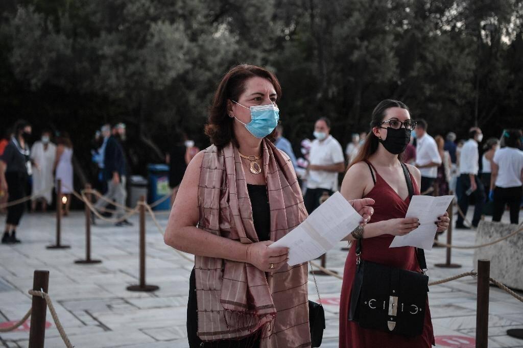 Des spectateurs portant un masque arrivent au théâtre antique Herodus Atticus au pied de l'Acropole pour un concert de l'Opéra national grec, à Athènes le 28 juillet 2020