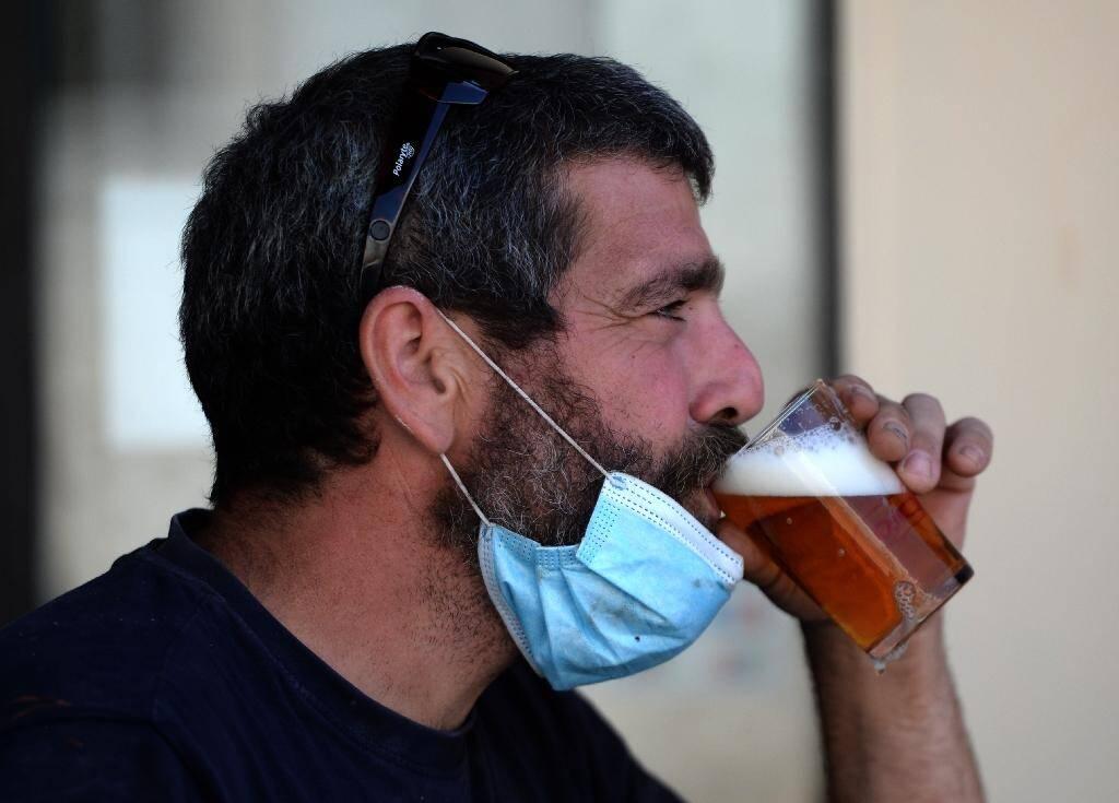 Un homme boit une bière en terrasse à Séville (Espagne) le 13 août 2020