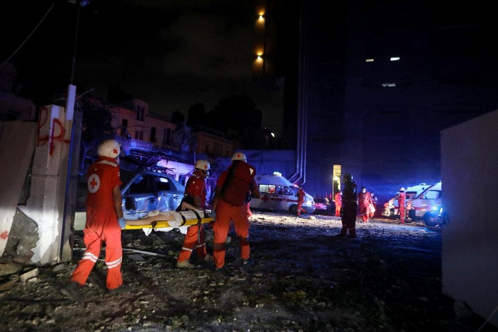 Des membres de la Croix-Rouge libanaise transporte une femme blessée dans les explosions du port de Beyrouth le 4 août 2020