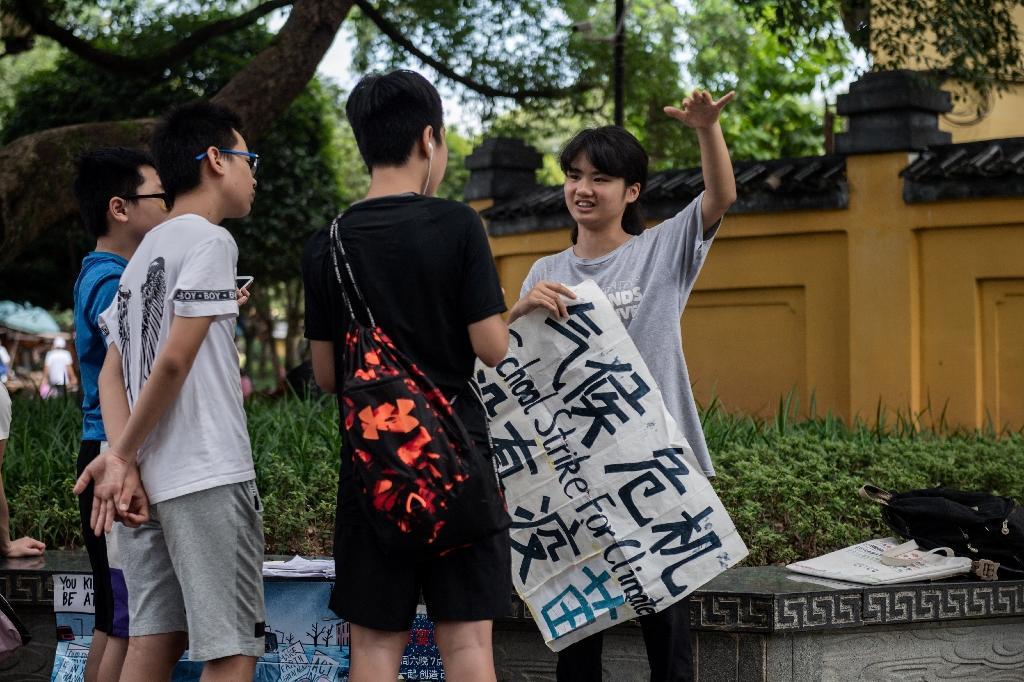 La militante écologique Howey Ou (à droite) parle avec des jeunes dans une rue de Guilin (Chine), le 7 août 2020