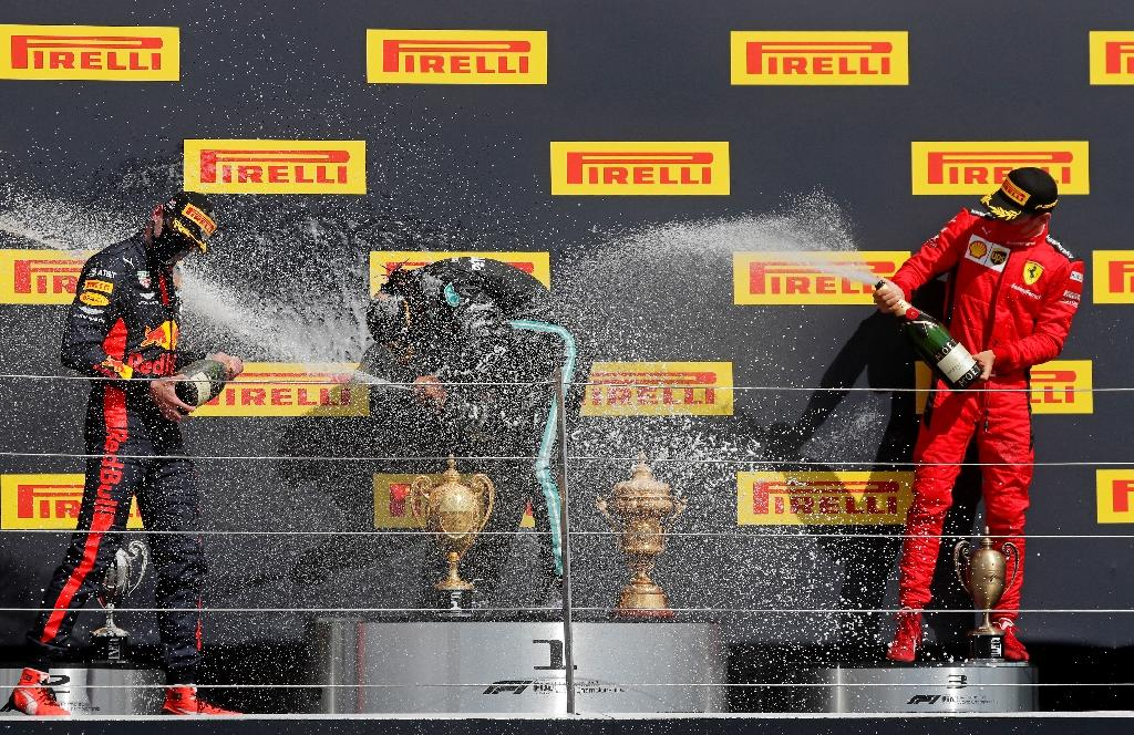 Le Britannique Lewis Hamilton (c) fête sa victoire avec le Néerlandais Max Verstappen (g), 2e, et le Monégasque Charles Leclerc, 3e, au GP de Grande-Bretagne, à Silverstone, le 2 août 2020