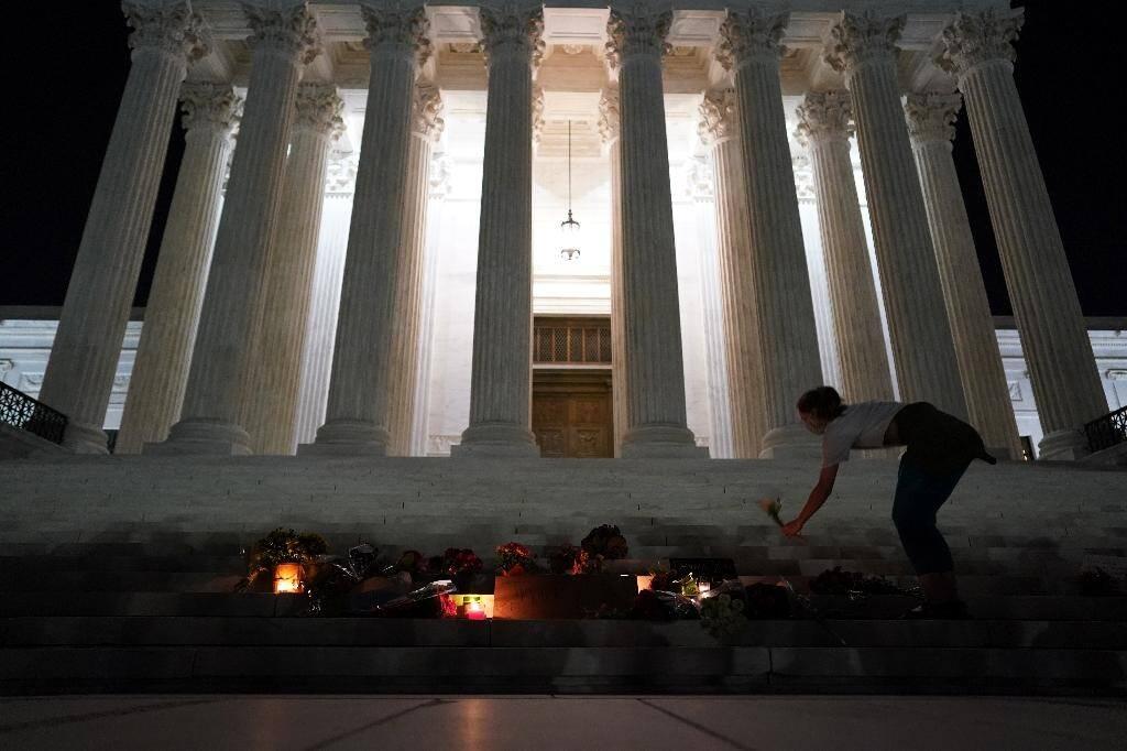 Des Américains déposent des fleurs et des bougies devant la Cour Suprême après la mort de la juge Ruth Bader Ginsburg, le 18 septembre 2020 à Washington