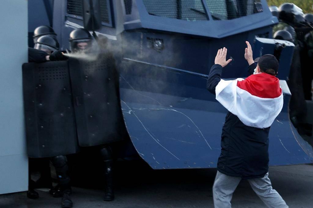 Un manifestant face aux policiers anti-émeute pendant une manifestation à Minsk, le 25 octobre 2020