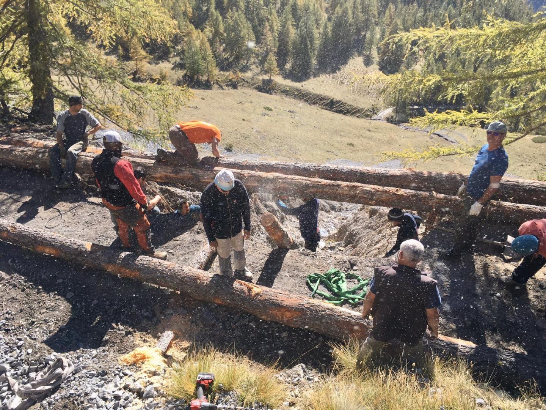 Avec des troncs de mélèzes, trouvés et coupés sur place, ces bûcherons volontaires ont créé un pont de toutes pièces en une journée.