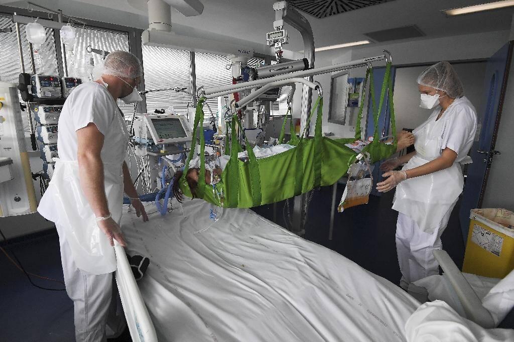 Des soignants prennent en charge un patient atteint du Covid-19 dans l'unité de soins intensifs de l'hôpital universitaire de Strasbourg, le 22 octobre 2020
