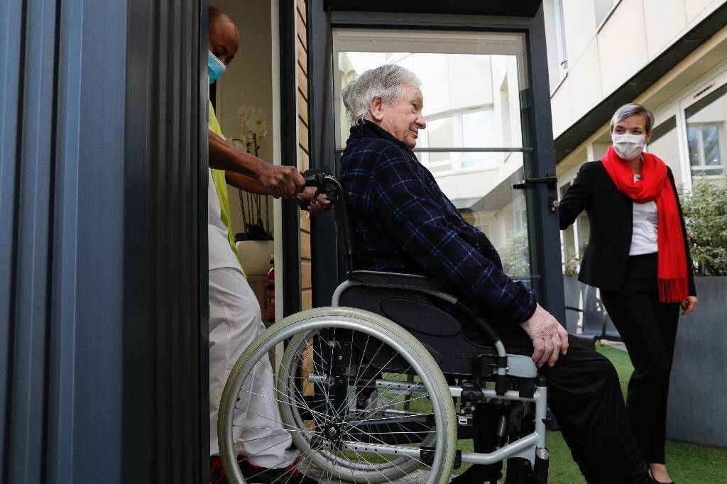 Une soignante aide Guy, 93 ans, à entrer dans un mobile-home où il va pouvoir déjeuner avec ses filles, le 12 novembre 2020 à l'Ehpad Beauregard de Villeneuve-Saint-Georges, près de Paris