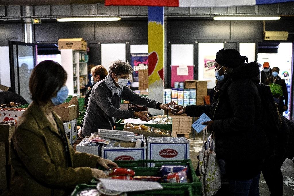 Des bénévoles des Restos du coeur distribuent une aide alimentaire à des personnes dans le besoin, le 13 octobre 2020 à Paris