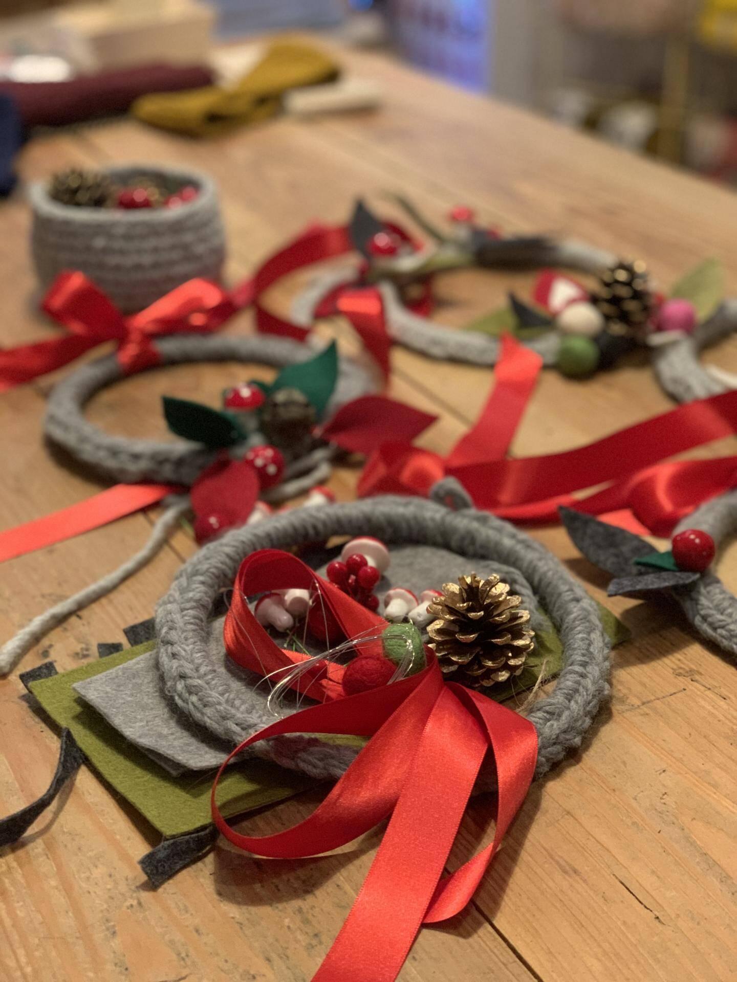 Pompons, pommes de pin et ruban servent à décorer les couronnes