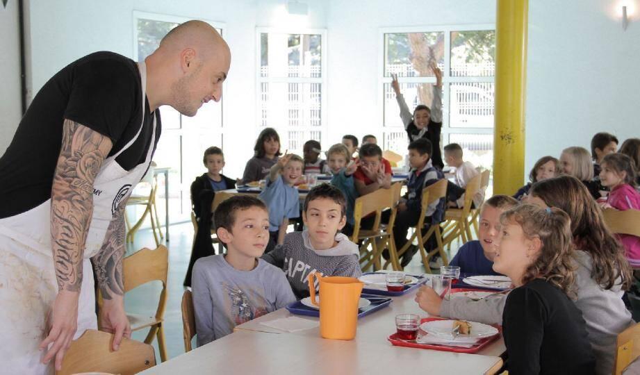 Un Masterchef à l'écoute des enfants dans le réfectoire de l'école.