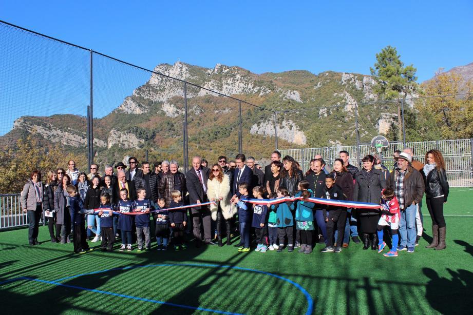 La population locale entoure les enfants et représentants de l'Etat lors de la coupe du ruban symbolique célébrant l'inauguration du terrain multisports.