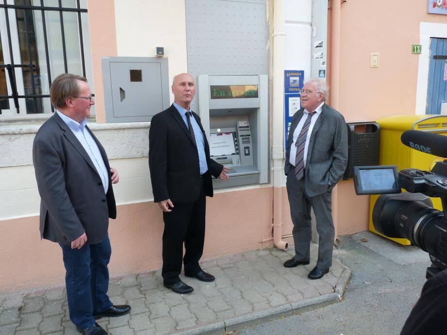 Devant La Poste de Néoules, André Guiol, Pierre-Yves Collombat et Robert Cecchinato observent comme un symbole l'écriteau indiquant que le distributeur de billets est hors service.