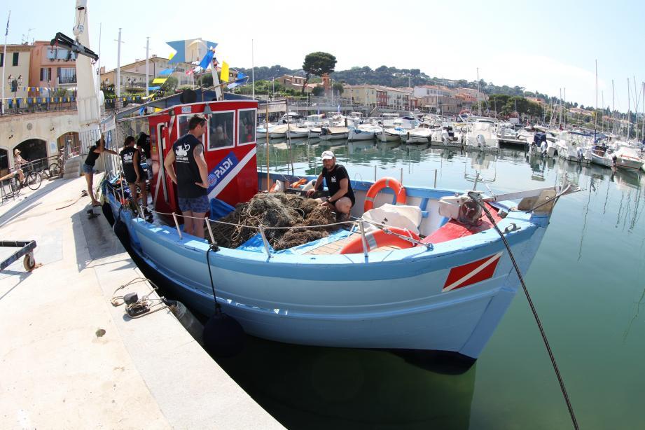 Accroupi dans le bateau, Manuel Dietrich devant le butin remonté.