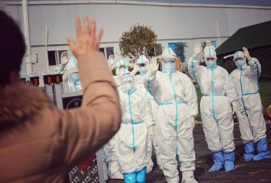 Des membres de l'équipe médicale disent au revoir, le 1er mars 2020, à une patiente guérie du coronavirus, dans l'un des hôpitaux provisoires de Wuhan installés pour faire face à l'épidémie