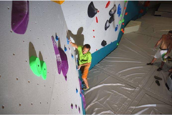Bruno, l'un des gérants du complexe, profite des plaisirs d'une grimpe après la mise en place des premiers blocs d'escalade.