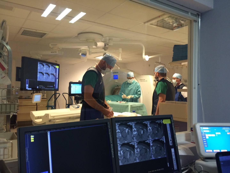 Une équipe de cinq personnes œuvrent autour du patient. Des écrans suivent en temps réel les opérations et permettent au médecin de guider son geste.