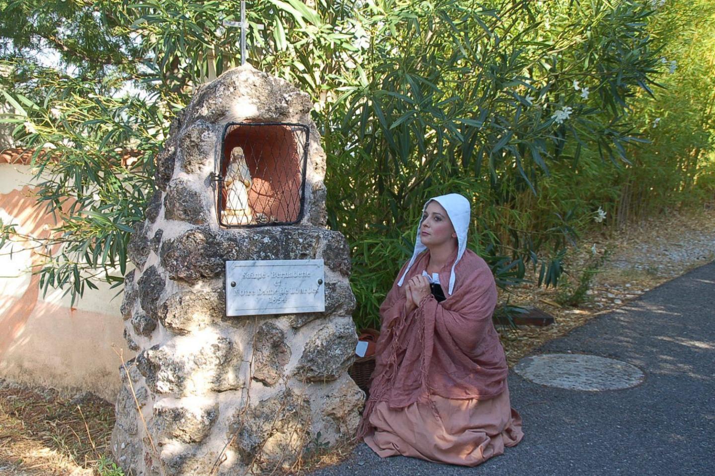 Fervente prière devant l'édifice dédié à Bernadette et Notre-Dame de Lourdes.
