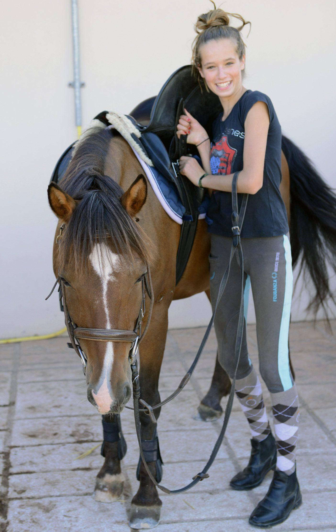 De retour dans son boxe, la cavalière descelle son cheval.