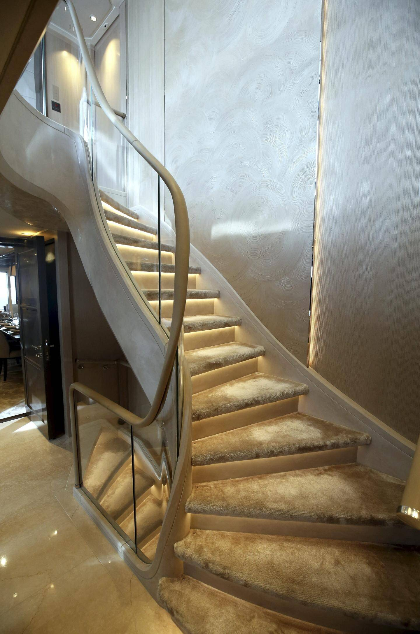 Cet escalier en aluminium et en plâtre orné d'une balustrade en verre trempé dessert trois étages